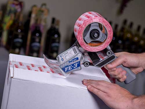 Hand applying packaging tape to a box using a hand dispenser